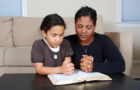 Minority woman and her daughter praying together